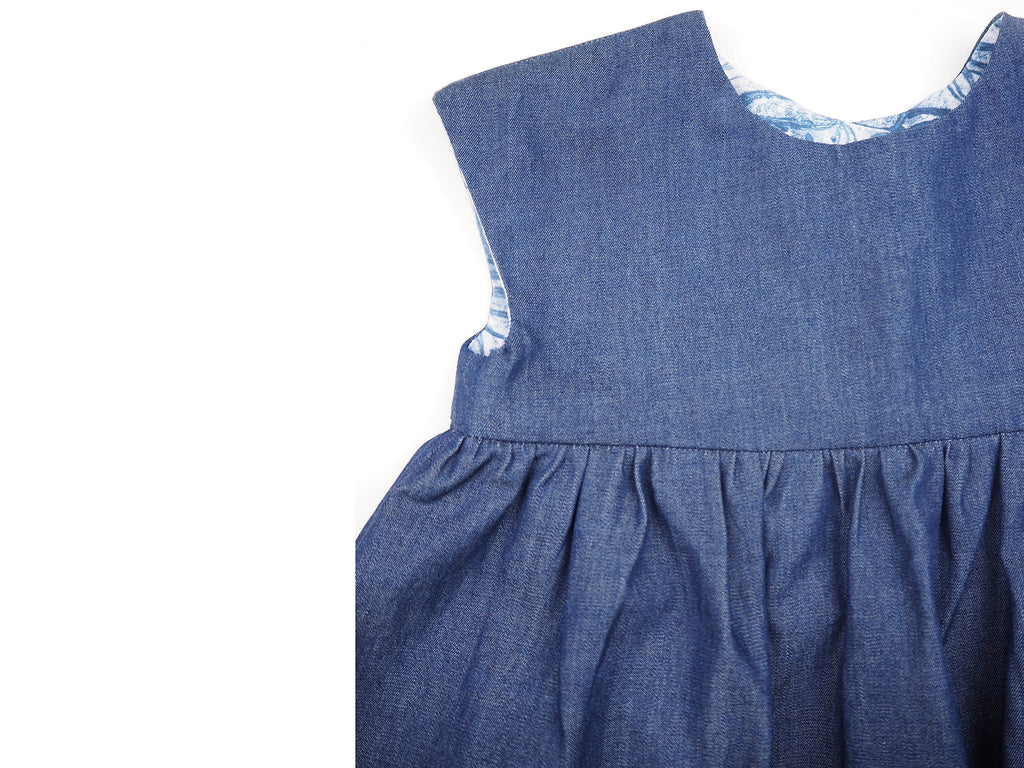 Close up of a handmade denim girl's dress with gathered skirt