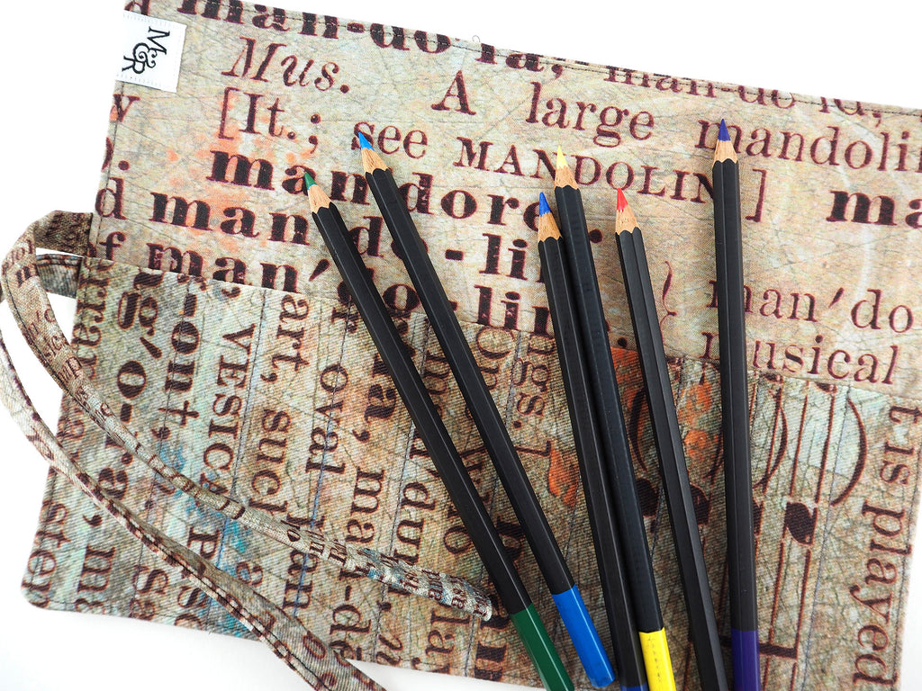 Handmade brush and pencil roll in text print fabric with pencils