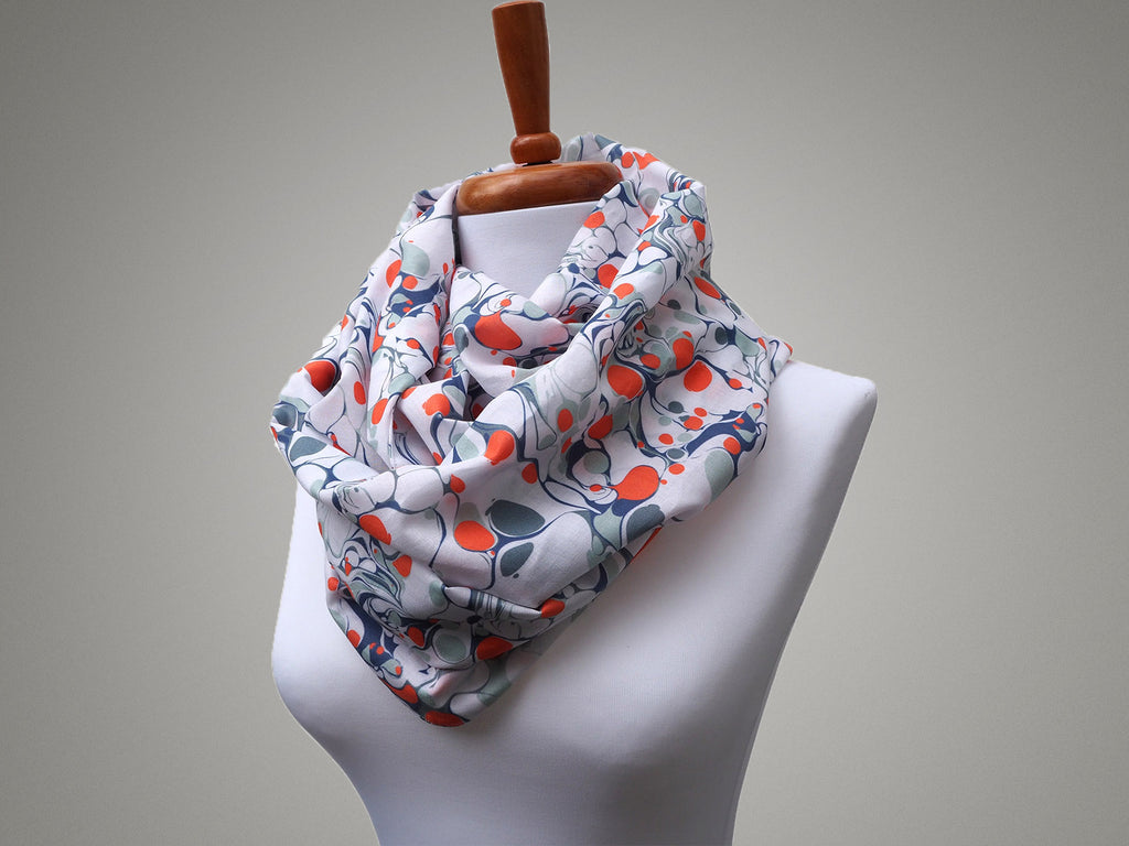 Handmade orange marble print infinity scarf on a mannequin