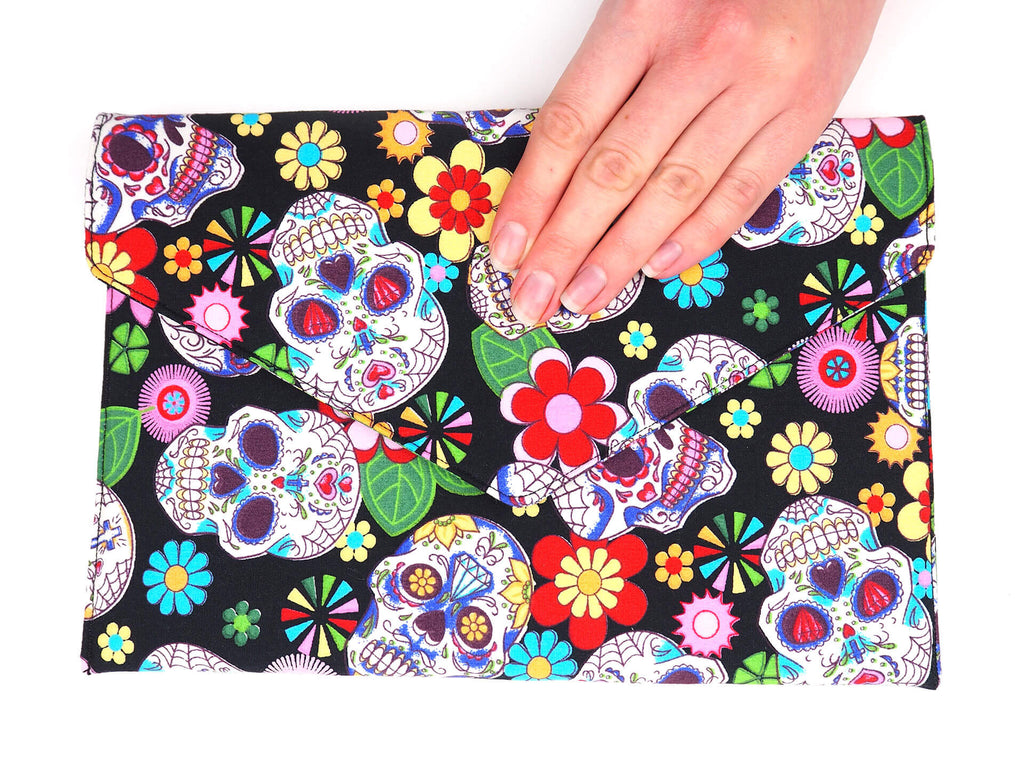 Hand holding a handmade envelope clutch in sugar skull print fabric