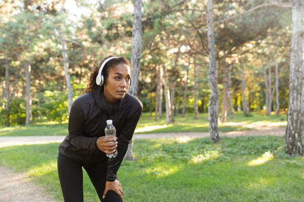 woman drinking water bottle for outdoor exercise