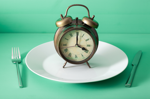 fork and knife crossed and alarm clock on plate