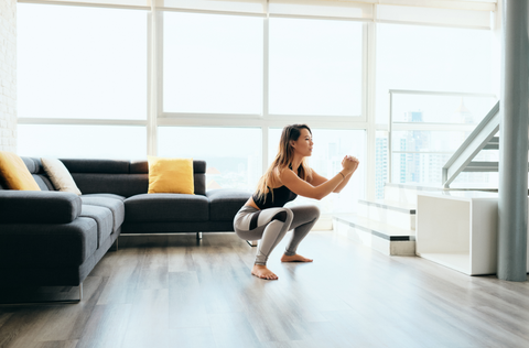 woman squatting in living room working out from home