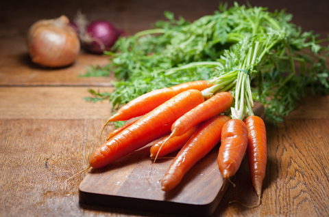 carrots with stems on wooden background