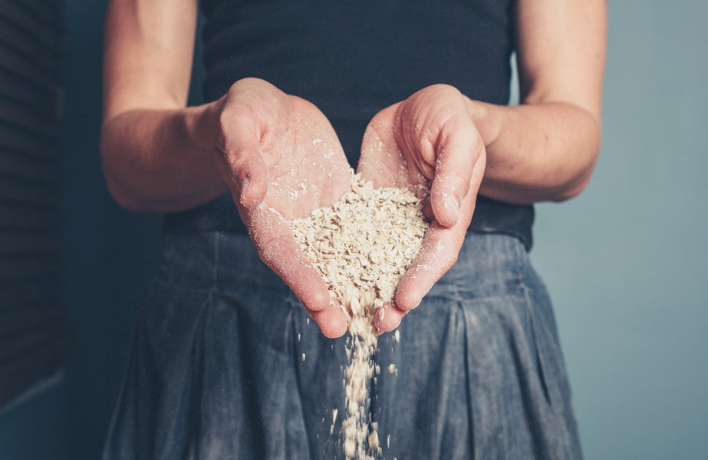 A young woman is standing with a handful of oats
