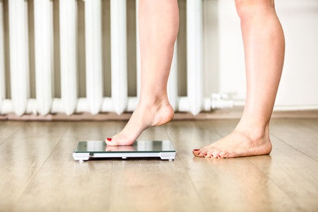 woman stepping tentatively on scale