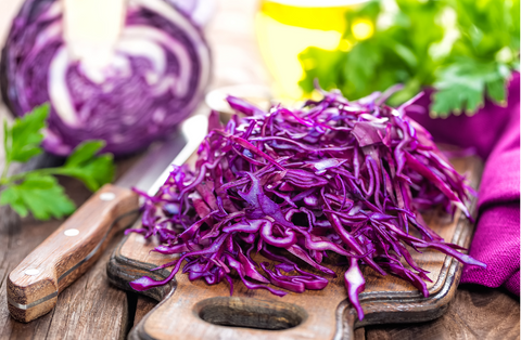 shredded red cabbage on wooden cutting board