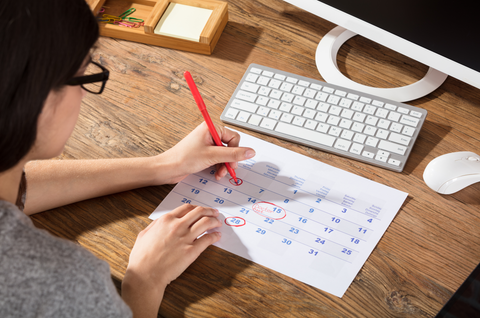 Woman Circling The Date On Calendar With Red Color Marker On Desk