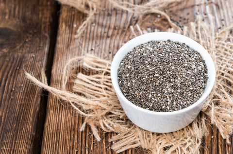 Chia Seeds in a small bowl (on dark wooden background)