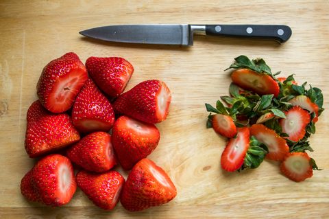 Freshly chopped strawberries on a chopping board with a knife