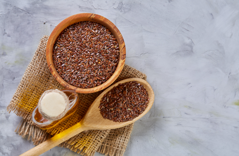 flax seeds in bowl and flaxseed oil in glass bottle on light textured background