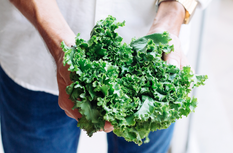 woman holding a bushel of kale