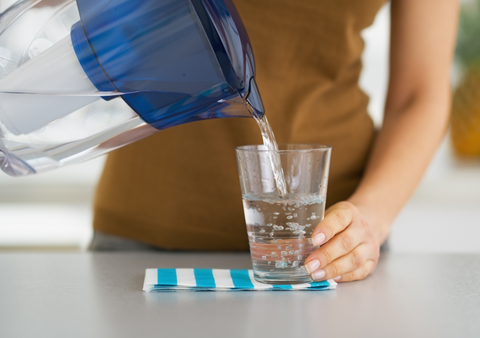 woman pouring water into glass from water filter pitcher