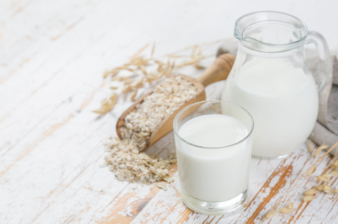 Oat milk in glass and jar on wood background
