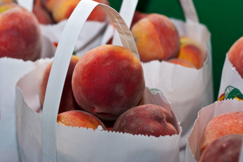 peaches in white paper bags
