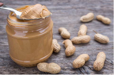 Jar of peanut butter with nuts. On wooden texture