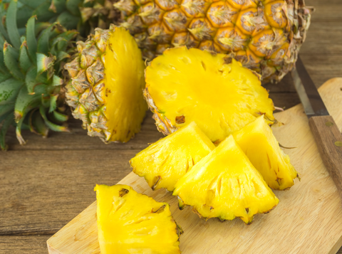 sliced pineapple on wooden cutting board