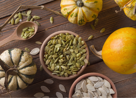 pumpkin seeds in bowl with pumpkins and gourds