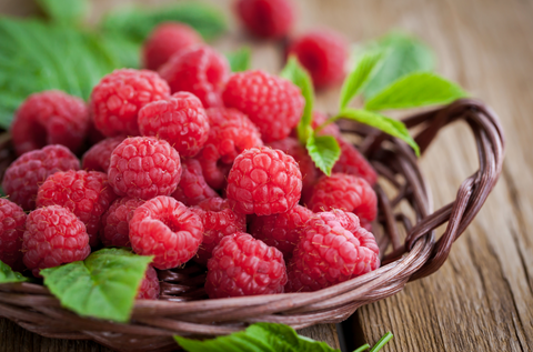 Fresh organic ripe raspberry with leaf in basket