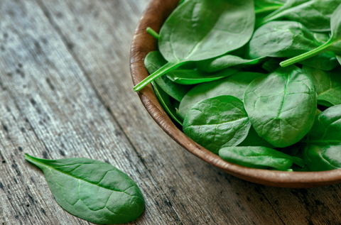 spinach in bowl on wooden background
