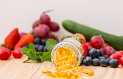 jar of supplements with fresh fruits and vegetables