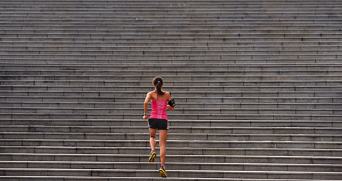 woman working out running up stairs outdoors for morning workout