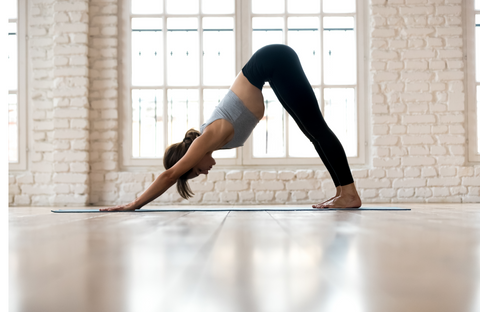 woman practicing yoga, doing Downward facing dog exercise