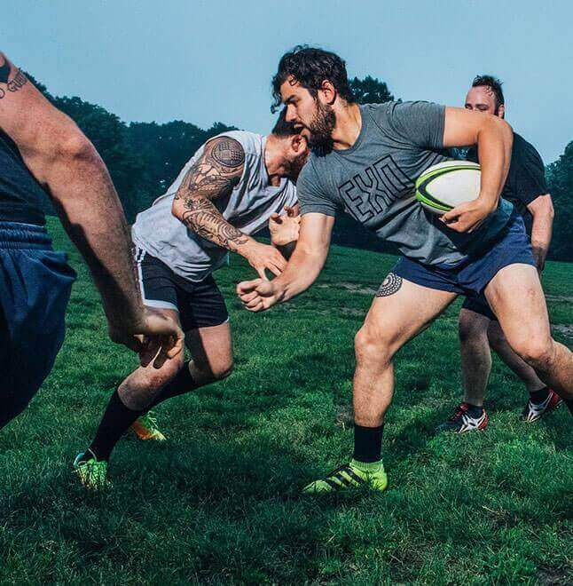 Four men playing rugby