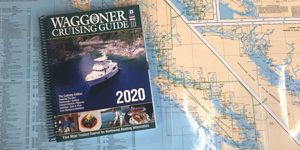 The 2020 Waggoner Cruising Guide, set on a Canadian Chart Catalog showing Inside Passage Nautical Chart Coverage
