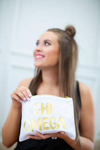 Girl holding Chi Omega cosmetic bag