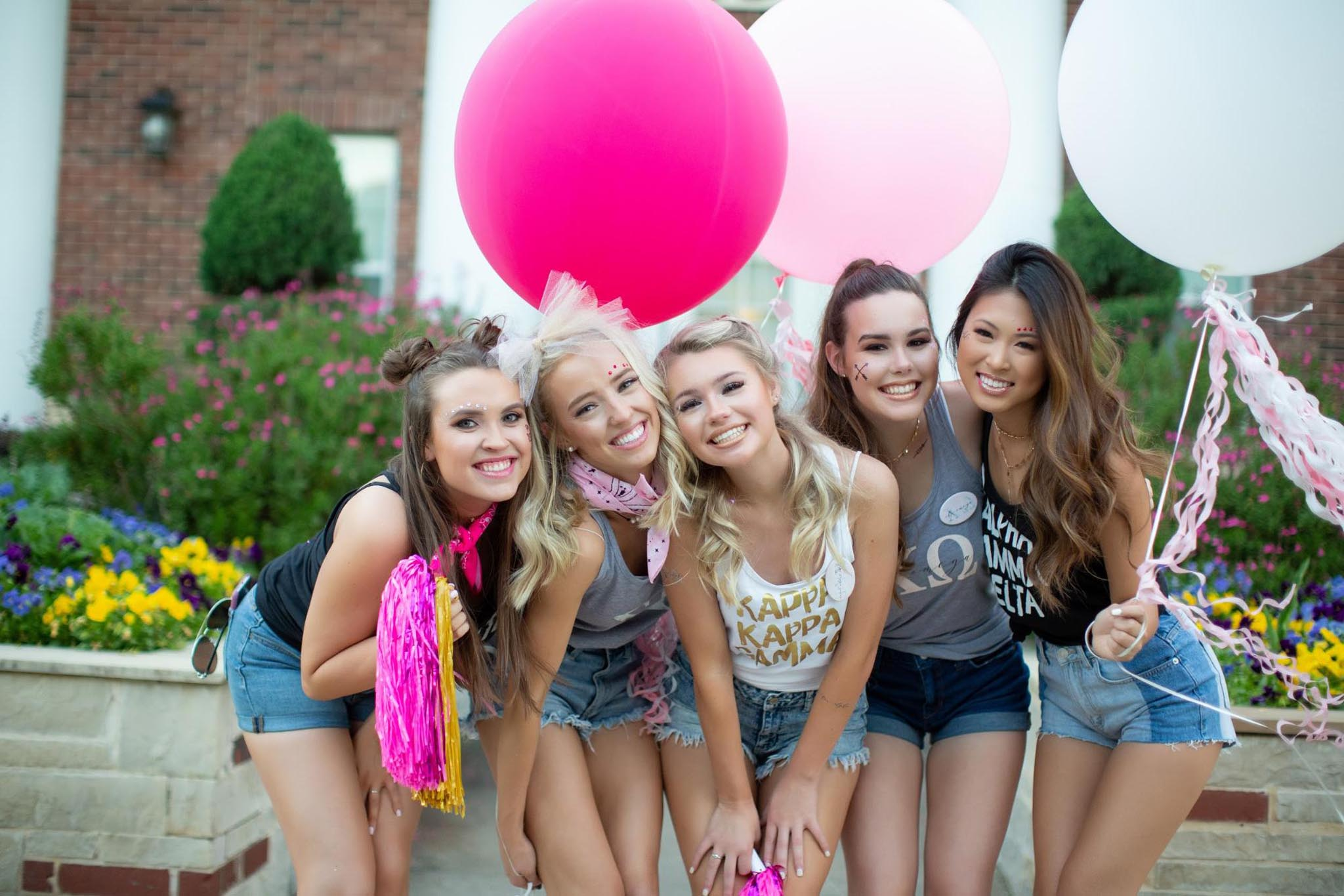 Sorority girls posing together holding large colorful balloons