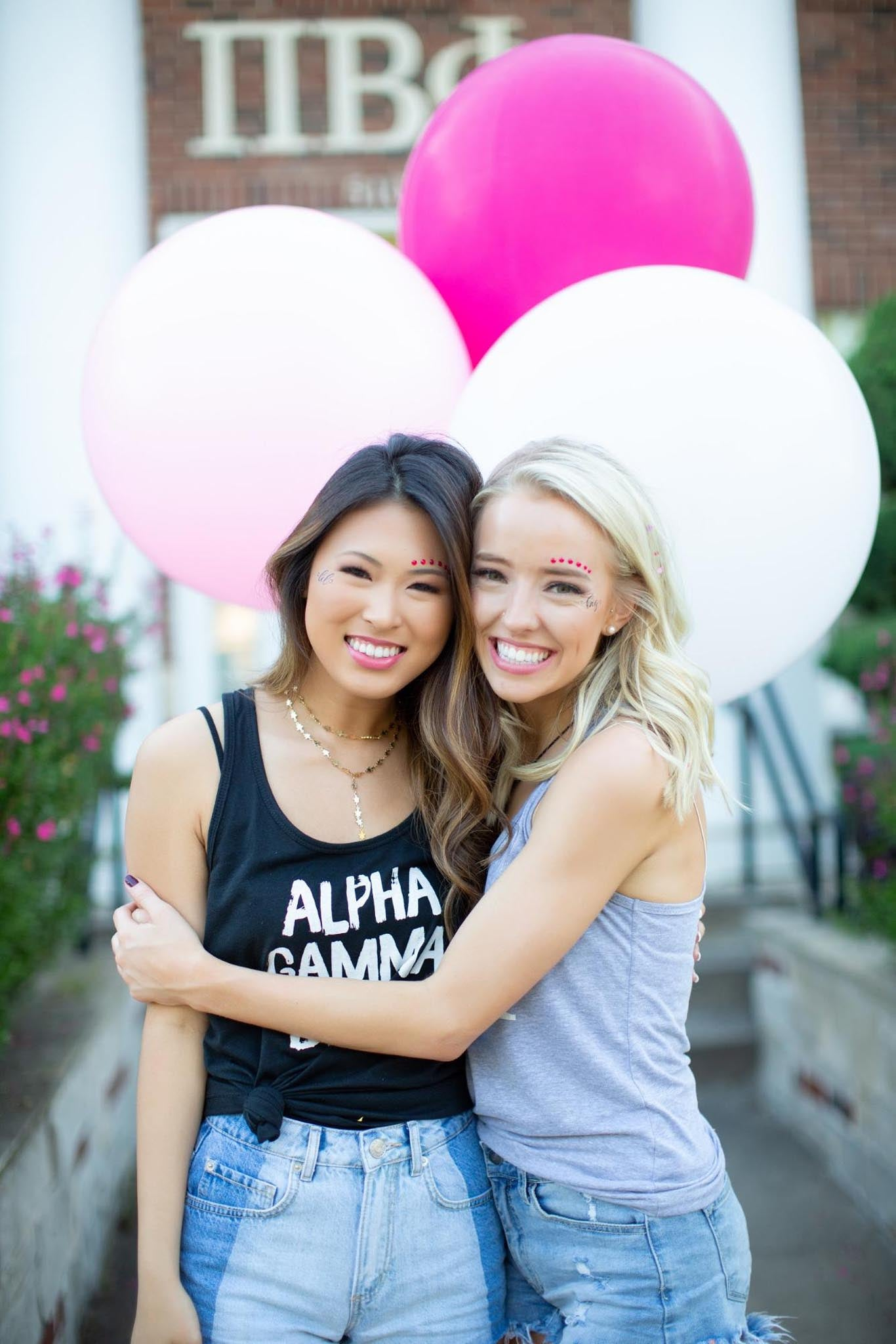 Girls posing in front of sorority house with balloons