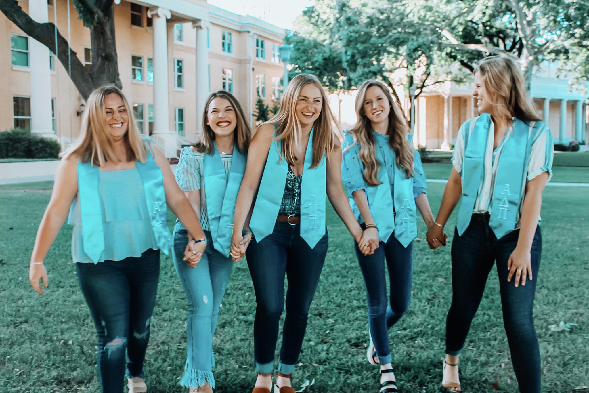 Sorority sisters walking together on campus with turquoise tinted clothing and background