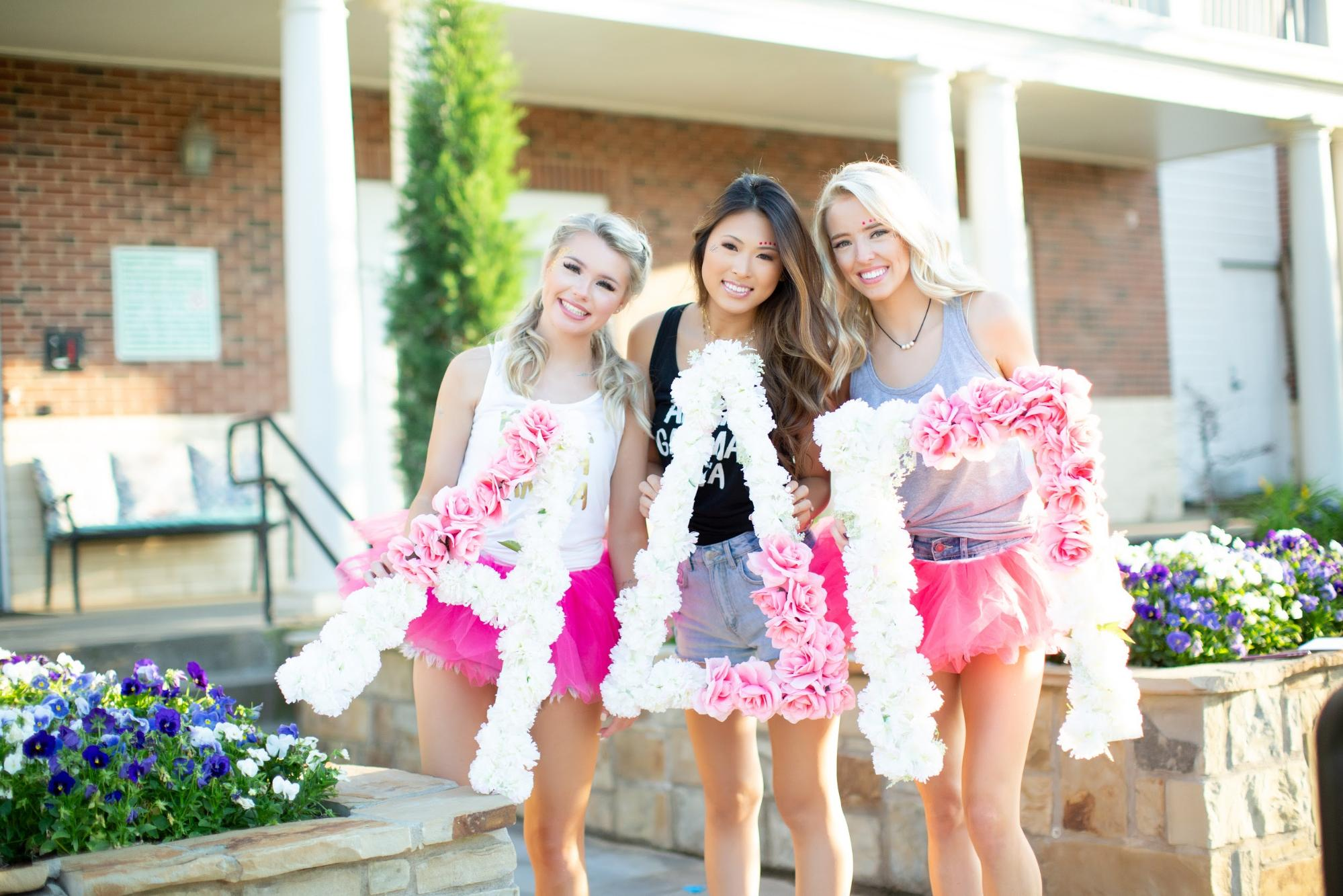 Sorority sisters holding up large floral greek letters