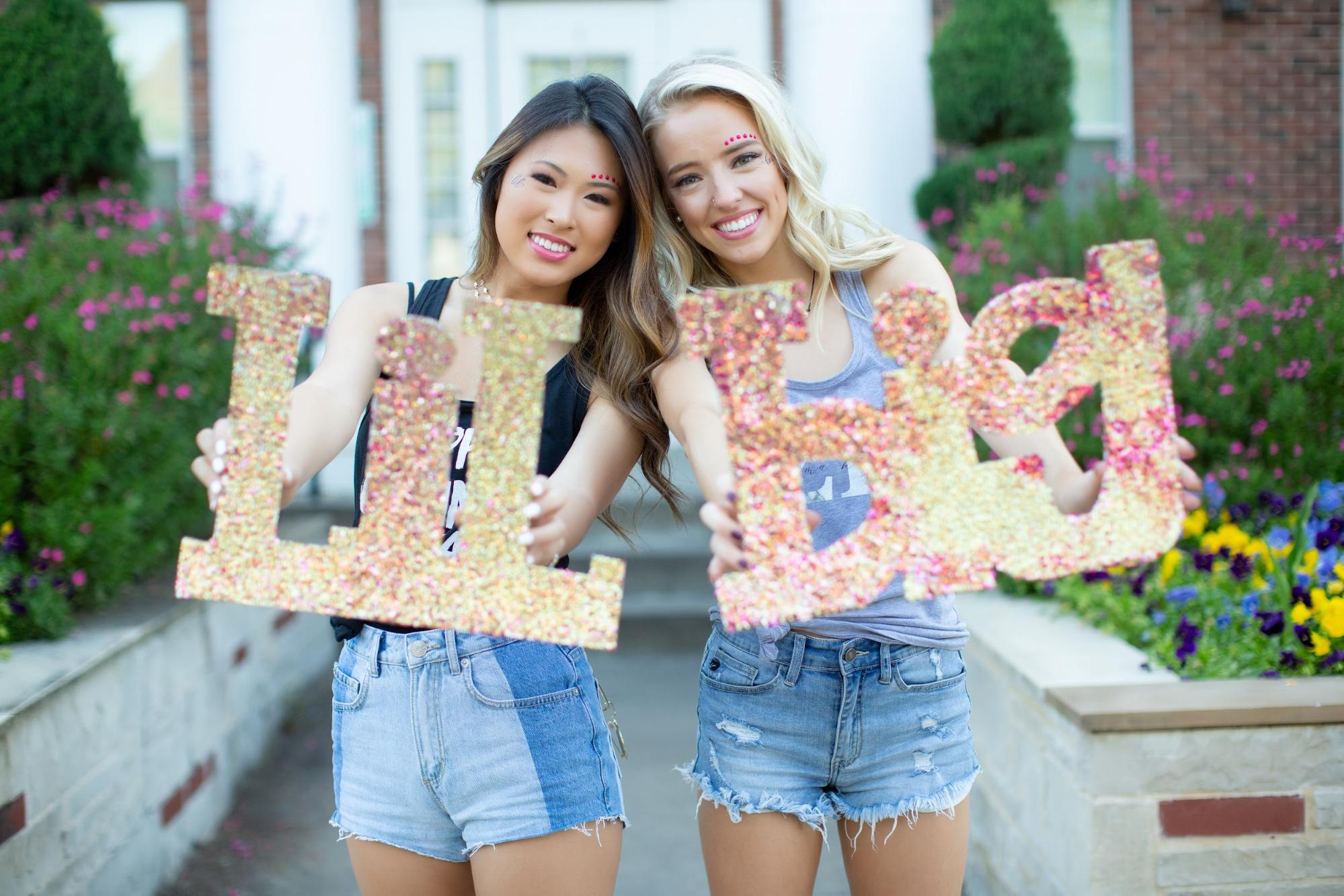 Sorority sisters holding large greek letters