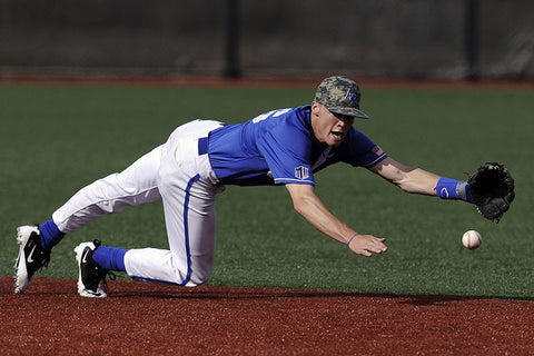 Baseball player lunging to catch a ball.