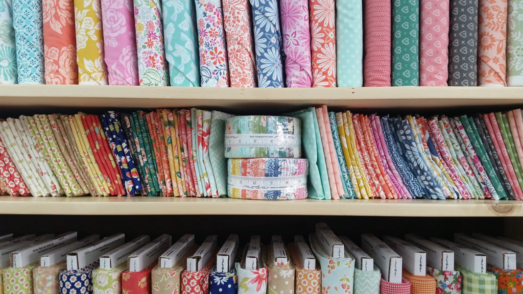 shelves stocked with fabric, fat quarters, and jelly rolls.