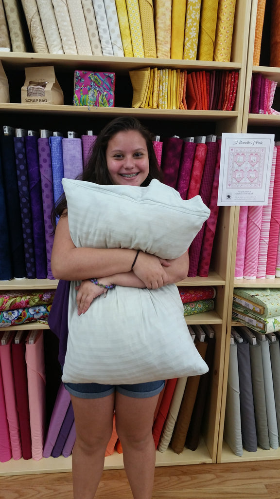 Isabel holding one of the finished pillows