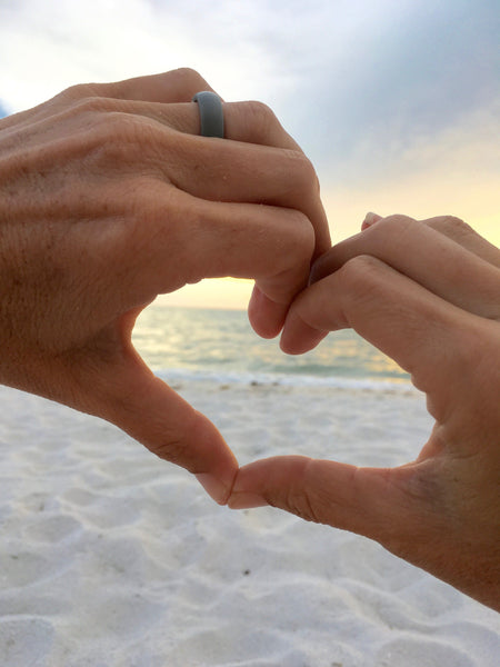 lady with hands forming a heart shape on the beach at sunset with grey silicone wedding ring on left finger