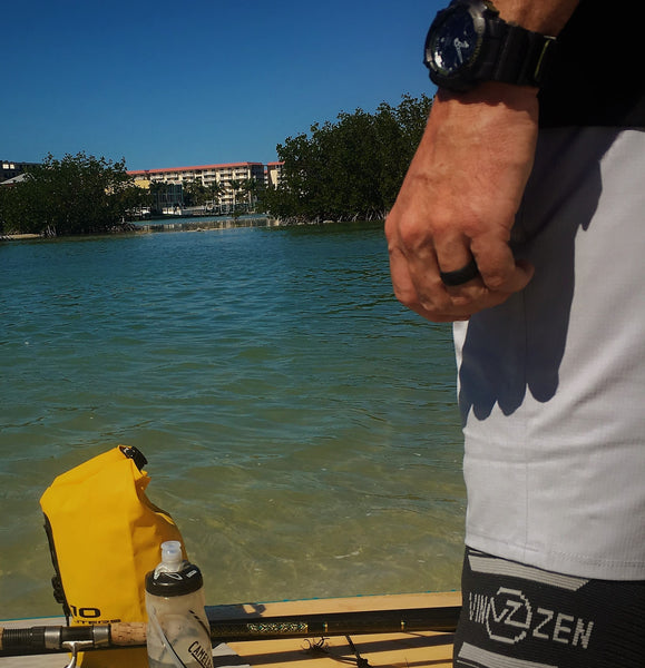 man wearing black silicone rubber ring similar to qalo enso honor outside while paddleboarding in ocean wearing knee sleeve and casio g shock watch