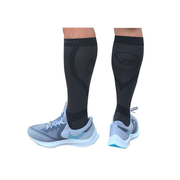 black compression socks vin zen with subtle grey design on a mans leg wearing nike shoes