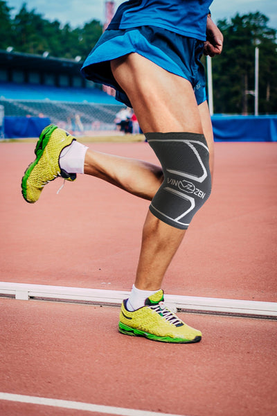 knee sleeves on a man while he runs on track strong legs knee protection support xompression knee sleeves