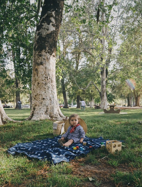 little girl on a picnic blanket