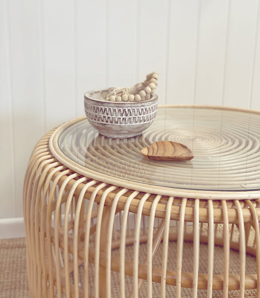 Bessie rattan coffee table with glass top styles with costal bowl and beads.