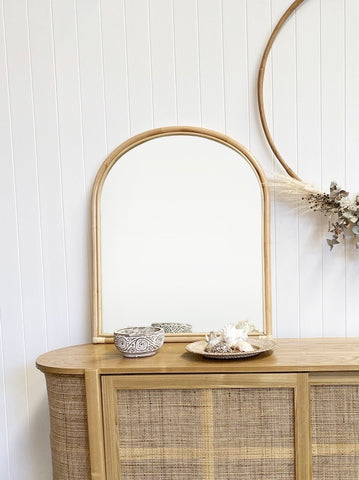 Asha Rattan Arched Mirror lent on top of the Florence Rattan Buffet and displayed with a few costal elements.