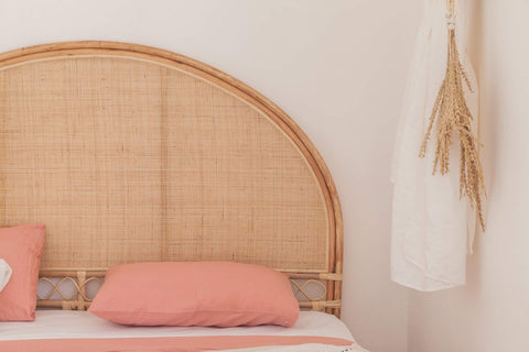 Koko Collective's Arched Natural Rattan Bedhead, displayed in a bedroom with linen curtains, bedding and other natural styling details.