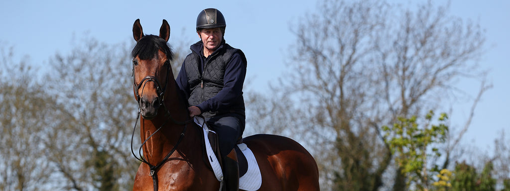 Nick Skelton wearing a Charles Owen riding hat while riding the horse