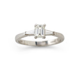 Emerald cut and tapered baguette cut diamond three stone engagement ring