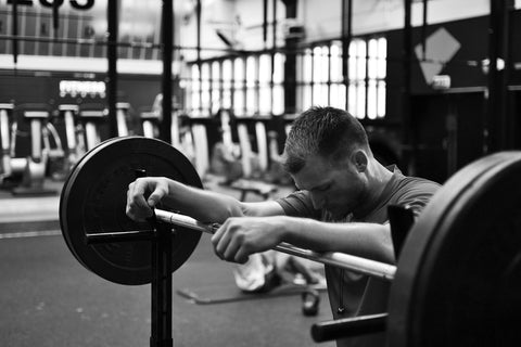 Man resting on his barbells