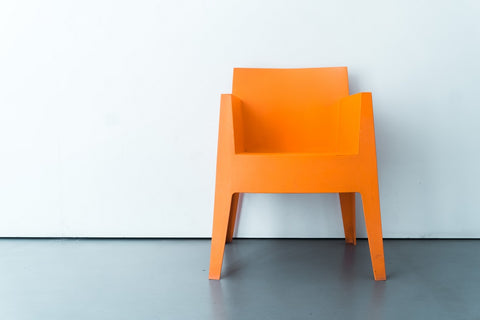 Bright orange chair infront of a white wall